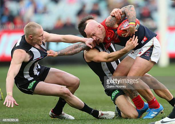 Nathan Jones of the Demons is tackled by Jack Frost and Levi Greenwood of the Magpies during the round 18 AFL match between the Collingwood Magpies...