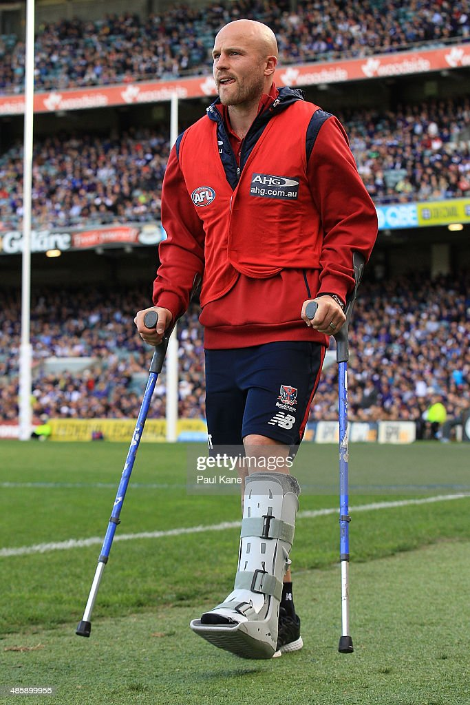 Nathan Jones of the Demons walks from the change rooms on crutches after being substituted out of the game during the round 22 AFL match between the...