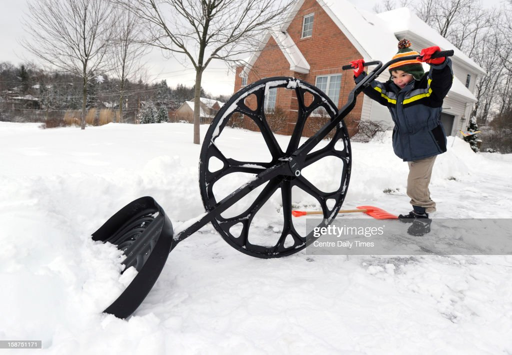 Nathan Lee, 5, uses a 'wovel' to remove snow from his driveway along Megan Drive in State College Pennsylvania, Thursday, December 27, 2012. A major winter storm hit Centre County Wednesday and the clean up continues.