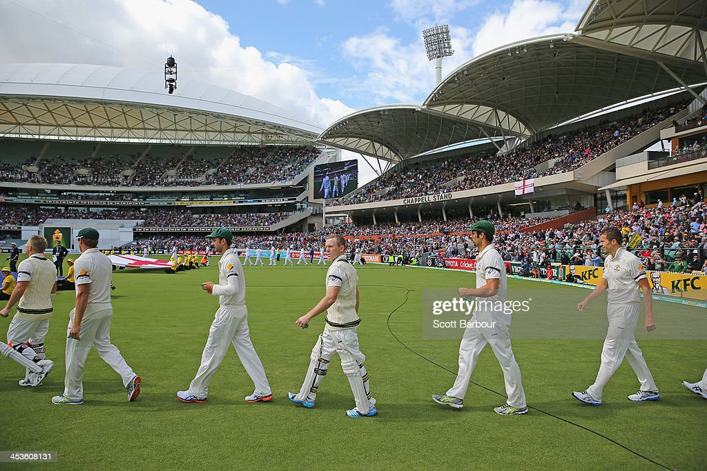Nathan Lyon, Chris Rogers and Mitchell Johnson of Australia walk onto the field for the national anthems during day one of the Second Ashes Test Match between Australia and England at Adelaide Oval on December 5, 2013 in Adelaide, Australia.