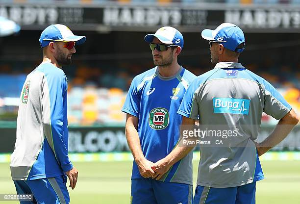 Nathan Lyon of Australia and Chadd Sayers of Australia talk during day one of the First Test match between Australia and Pakistan at The Gabba on...