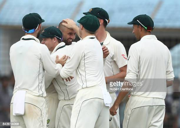 Nathan Lyon of Australia and Pat Cummins celebrate after they combined to dismiss Mominul Haque of Bangladesh during day four of the Second Test...