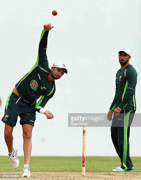 Nathan Lyon of Australia bowls as Fawad Ahmed of Australia looks on during an Australian nets session at Windsor Park on May 31 2015 in Roseau...