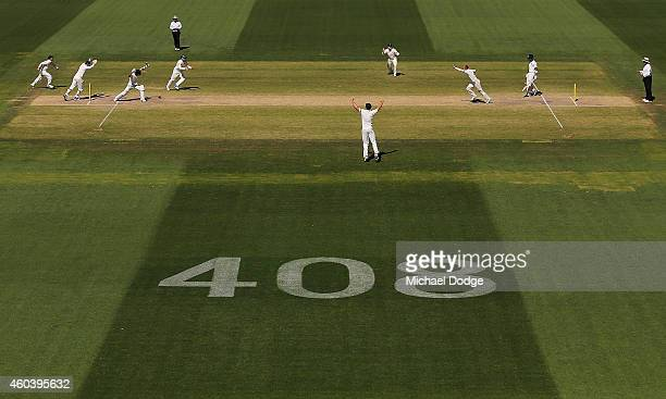 Nathan Lyon of Australia celebrates the wicket of Ajinkya Rahane of India with teamates with the number 408 displayed dedicated to the late Phillip...