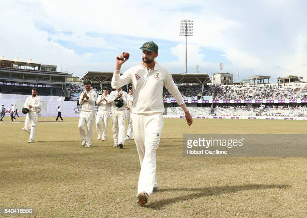 Nathan Lyon of Australia holds up the ball after taking five wickets in the innings during day three of the First Test match between Bangladesh and...