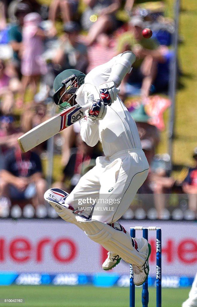 Nathan Lyon of Australia jumps as he plays a shot during day three of the first cricket Test match between New Zealand and Australia at the Basin Reserve in Wellington on February 14, 2016. / AFP / Marty Melville