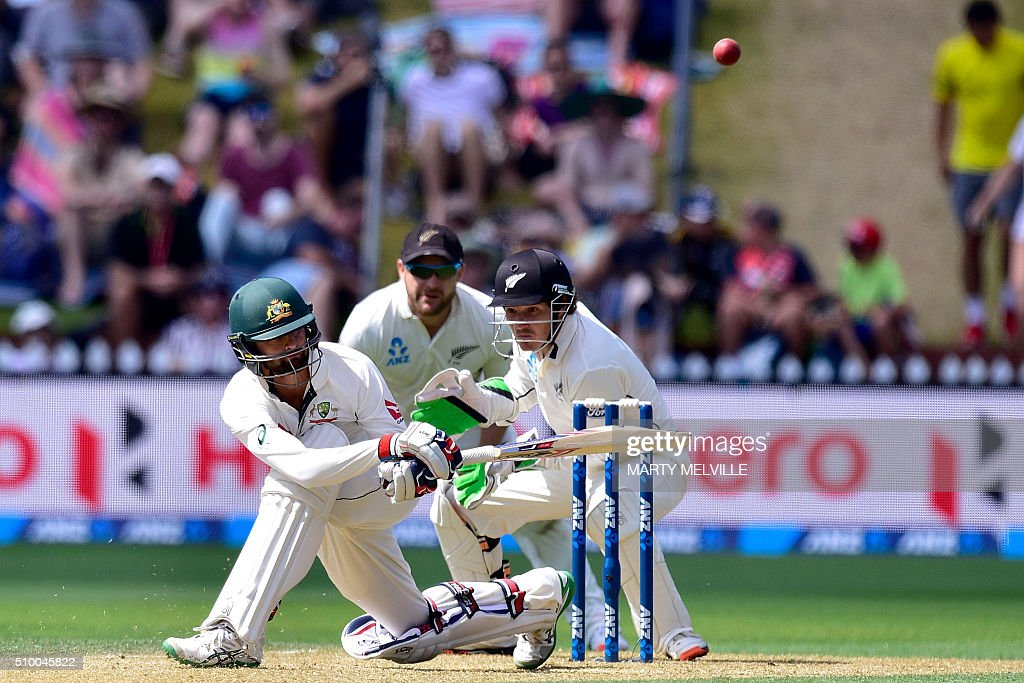 Nathan Lyon (L) of Australia plays a shot watched by New Zealand captain Brendon McCullum (C and keeper BJ Watling (R) during day three of the first cricket Test match between New Zealand and Australia at the Basin Reserve in Wellington on February 14, 2016. / AFP / Marty Melville