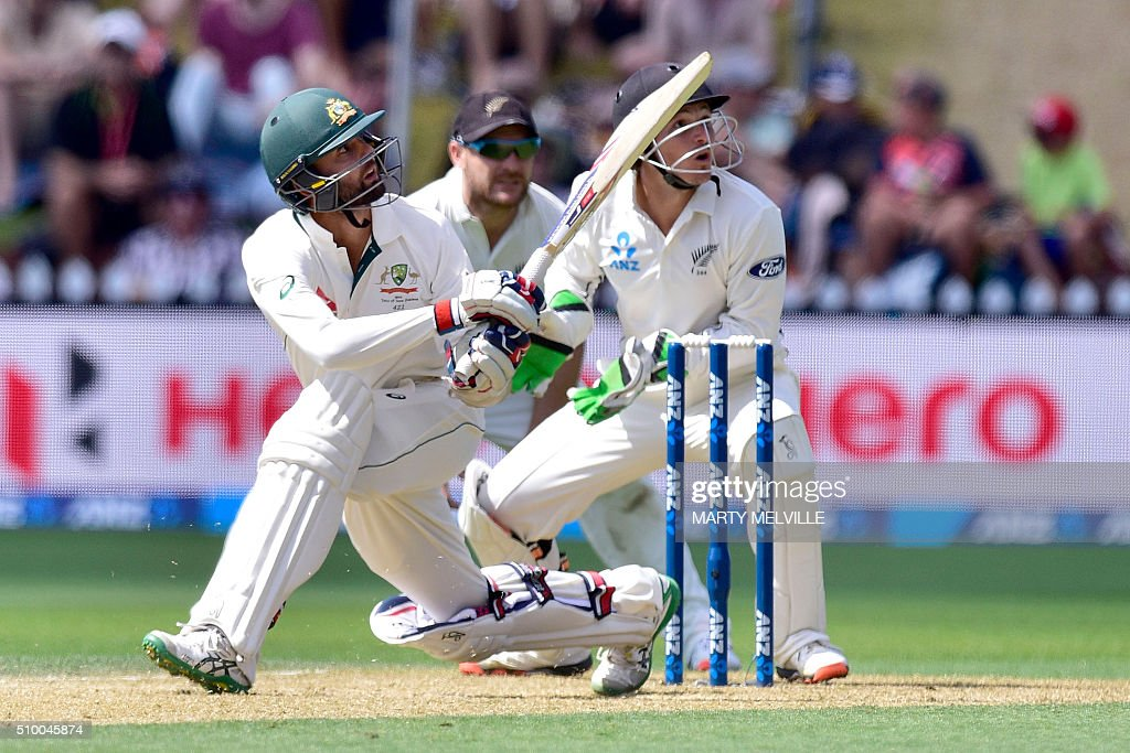 Nathan Lyon (L) of Australia plays a shot watched by New Zealand captain Brendon McCullum (C) and keeper BJ Watling (R) during day three of the first cricket Test match between New Zealand and Australia at the Basin Reserve in Wellington on February 14, 2016. / AFP / Marty Melville
