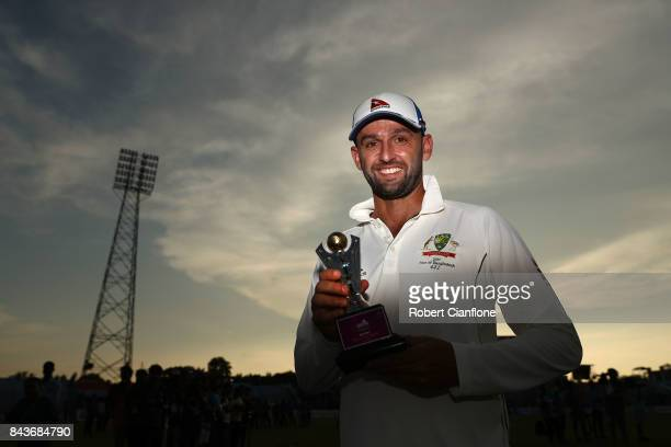 Nathan Lyon of Australia poses with the Man of the Match trophy after Australia defeated Bangladesh on day four of the Second Test match between...