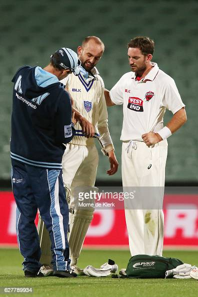 Nathan Lyon of the NSW Blues receives treatment after being struck by the ball on his right arm during day one of the Sheffield Shield match between...