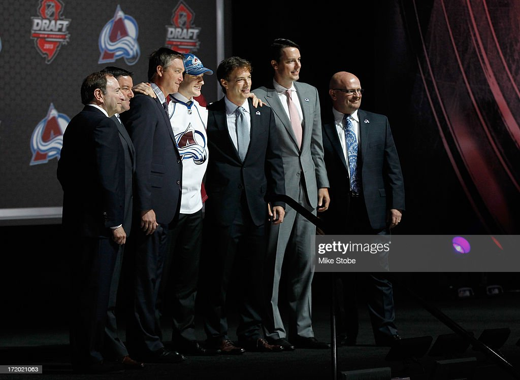 Nathan MacKinnon, #1 overall draft pick in the first round by the Colorado Avalanche, poses on stage with members of the Avalanche organization including head coach Patrick Roy (3rd L) and Executive Vice President of Hockey Operations Joe Sakic (3rd R), during the 2013 NHL Draft at the Prudential Center on June 30, 2013 in Newark, New Jersey.