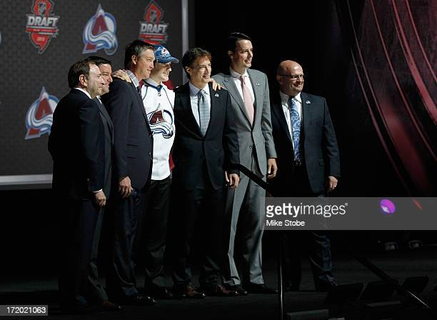 Nathan MacKinnon #1 overall draft pick in the first round by the Colorado Avalanche poses on stage with members of the Avalanche organization...