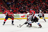Nathan MacKinnon of the Colorado Avalanche battles for the puck against Matt Niskanen of the Washington Capitals in the first period during an NHL...