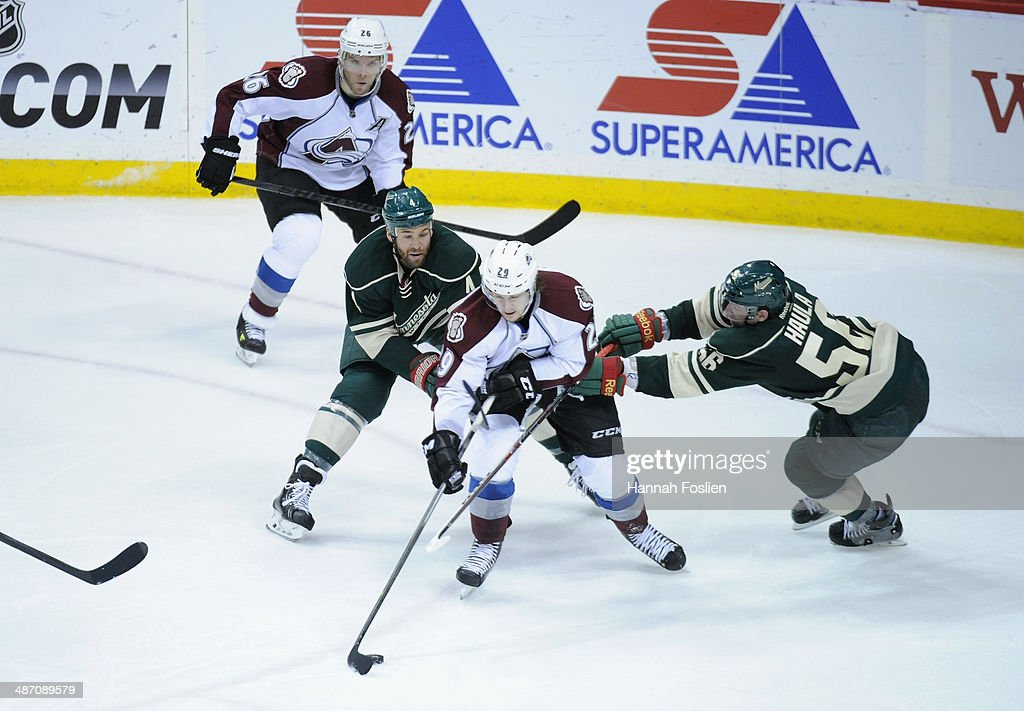 <a gi-track='captionPersonalityLinkClicked' href=/galleries/search?phrase=Nathan+MacKinnon&family=editorial&specificpeople=8610127 ng-click='$event.stopPropagation()'>Nathan MacKinnon</a> #29 of the Colorado Avalanche controls the puck against <a gi-track='captionPersonalityLinkClicked' href=/galleries/search?phrase=Clayton+Stoner&family=editorial&specificpeople=2222214 ng-click='$event.stopPropagation()'>Clayton Stoner</a> #4 and <a gi-track='captionPersonalityLinkClicked' href=/galleries/search?phrase=Erik+Haula&family=editorial&specificpeople=5894652 ng-click='$event.stopPropagation()'>Erik Haula</a> #56 of the Minnesota Wild in Game Four of the First Round of the 2014 NHL Stanley Cup Playoffs on April 24, 2014 at Xcel Energy Center in St Paul, Minnesota. The Wild defeated the Avalanche 2-1.