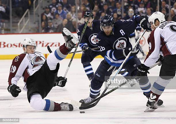Nathan MacKinnon of the Colorado Avalanche gets tripped up as he fights for the puck with Blake Wheeler of the Winnipeg Jets in second period action...