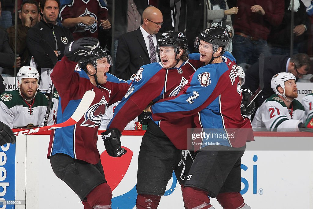 Nathan MacKinnon #29 of the Colorado Avalanche is congratulated by teammates Paul Stastny #26 and Nick Holden #2 after scoring his first career playoff goal against the Minnesota Wild in Game Two of the First Round of the 2014 Stanley Cup Playoffs at the Pepsi Center on April 19, 2014 in Denver, Colorado.