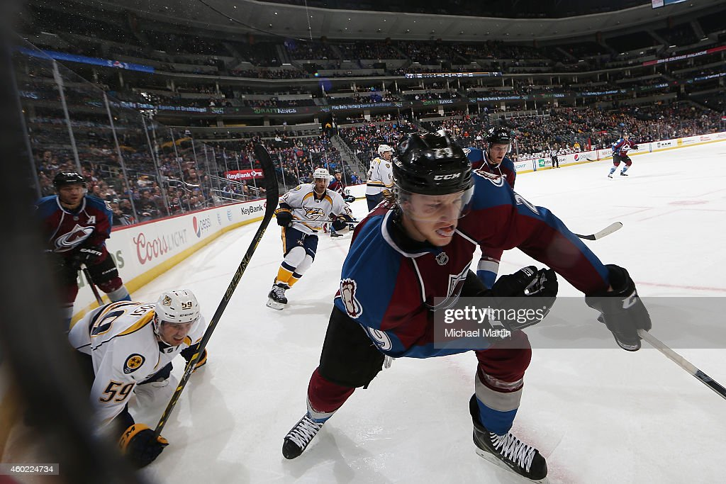 Nathan MacKinnon #29 of the Colorado Avalanche skates for the puck as Roman Josi #59 of the Nashville Predators looks on at the Pepsi Center on December 9, 2014 in Denver, Colorado. The Predators defeated the Avalanche 3-0.