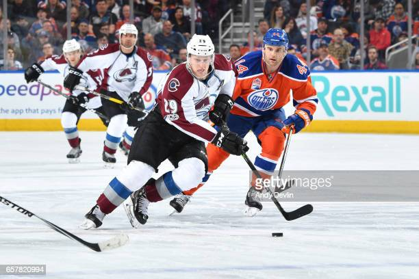 Nathan MacKinnon of the Colorado Avalanche skates with the puck while being pursued by Zack Kassian of the Edmonton Oilers on March 25 2017 at Rogers...