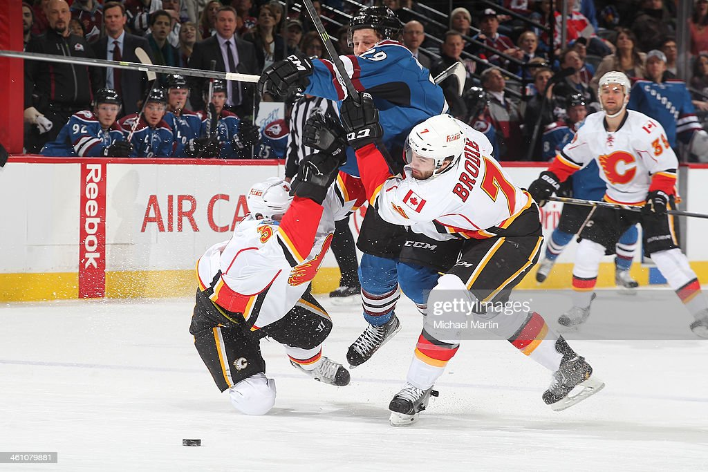 Nathan MacKinnon #29 of the Colorado Avalanche tries to blast through TJ Brodie #7 and Ladislav Smid #3 of the Calgary Flames at the Pepsi Center on January 06, 2014 in Denver, Colorado.