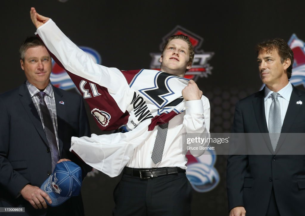 Nathan MacKinnon (c) puts on his Colorado Avalanche jersey as he stands with head coach Patrick Roy (l) and Joe Sakic (r) after MacKinnon was selected number one overall in the first round by Colorado during the 2013 NHL Draft at the Prudential Center on June 30, 2013 in Newark, New Jersey.
