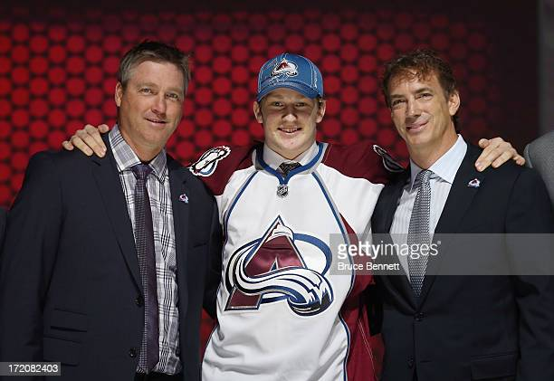 Nathan MacKinnon puts on his Colorado Avalanche jersey as he stands with head coach Patrick Roy and Joe Sakic after MacKinnon was selected number one...