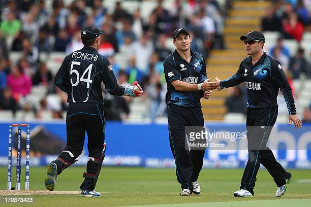 Nathan McCullum is congratulated by brother Brendon McCullum and Luke Ronchi of New Zealand after bowling George Bailey of Australia during the ICC...