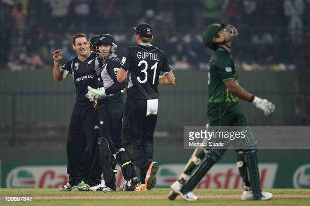Nathan McCullum of New Zealand celebrates taking the wicket of Umar Akmal with Brendon McCullum and Martin Guptill during the New Zealand v Pakistan...