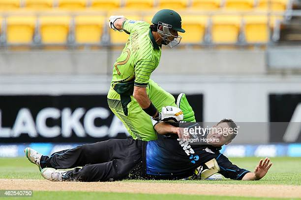 Nathan McCullum of New Zealand collides with MisbahulHaq of Pakistan while attempting to field off his own bowling during the One Day International...