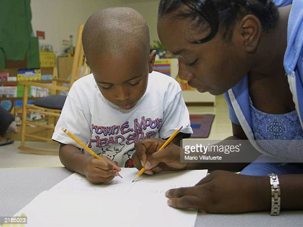 Nathan Miller works on printing his name with the help of Sharae Morgan a teacher's aide at the Brown E Moore Head Start Center July 22 2003 in...
