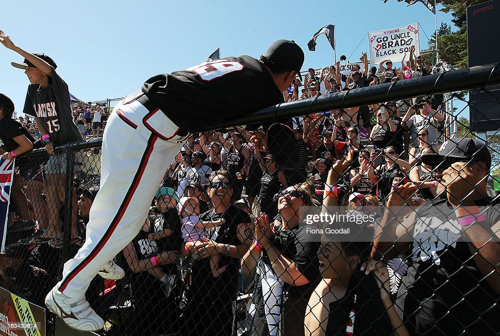 Nathan Nukunuku leaps the fence to friends and family of the The Black Sox while celebrating victory in the Softball World Championship over Venezuela at Tradstaff Sports Stadium on March 10, 2013 in Auckland, New Zealand.