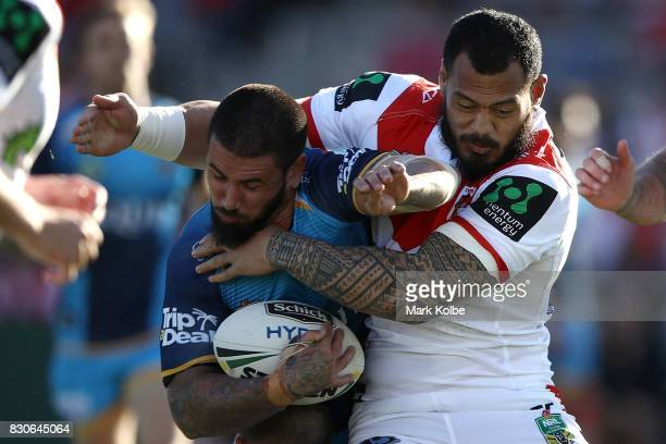 Nathan Peats of the Titans is tackled by Leeson Ah Mau of the Dragons during the round 23 NRL match between the St George Illawarra Dragons and the...