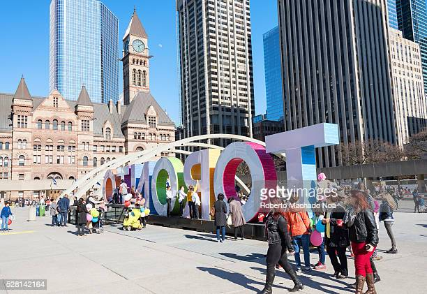 Nathan Philips Square People sitting near Toronto multicolor sign