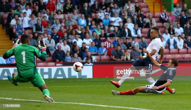 Nathan Redmond of England U21 scores the opening goal past Jordan Archer of Scotland U21 during the Kick It Out International between England U21 and...