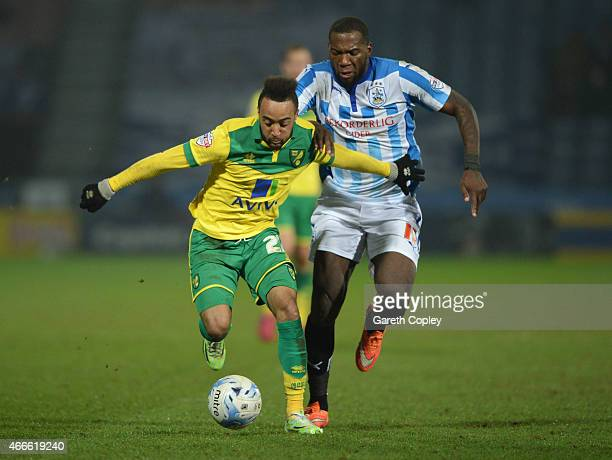 Nathan Redmond of Norwich City is chased by Ishmael Miller of Huddersfield Town during the Sky Bet Championship match between Huddersfield Town and...
