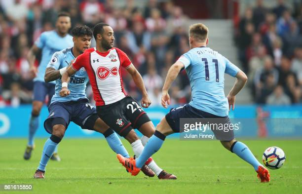 Nathan Redmond of Southampton takes on DeAndre Yedlin and Matt Ritchie of Newcastle United during the Premier League match between Southampton and...