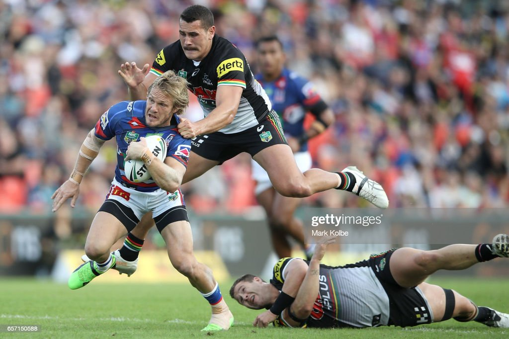 Nathan Ross of the Knights is tackled by Reagan Campbell-Gillard of the Panthers as he jumps over Trent Merrin of the Panthers during the round four NRL match between the Penrith Panthers and the Newcastle Knights at Pepper Stadium on March 24, 2017 in Sydney, Australia.