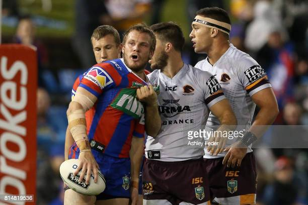 Nathan Ross of the Knights is tackled by the Broncos during the round 19 NRL match between the Newcastle Knights and the Brisbane Broncos at McDonald...