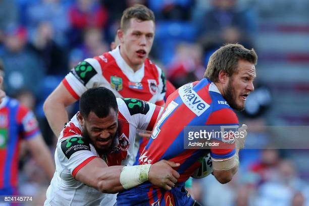 Nathan Ross of the Knights is tackled by the Dragons defence during the round 21 NRL match between the Newcastle Knights and the St George Illawarra...