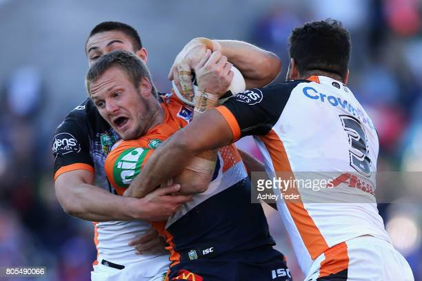 Nathan Ross of the Knights is tackled by the Tigers defence during the round 17 NRL match between the Newcastle Knights and the Wests TIgers at...