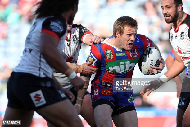 Nathan Ross of the Knights is tackled during the round 22 NRL match between the Newcastle Knights and the New Zealand Warriors at McDonald Jones...