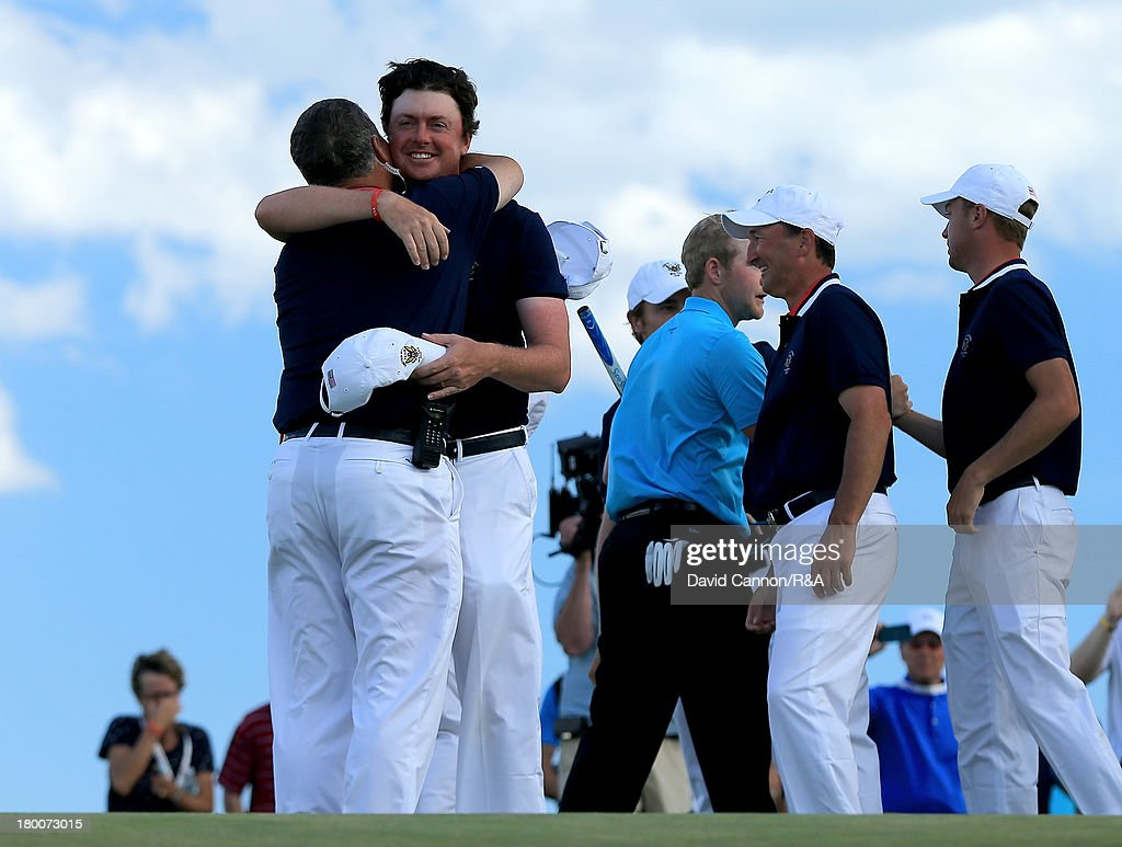 Nathan Smith of the United States team is embraced by his captain Jim Holtgrieve as Smith secured the winning point by beating Nathan Kimsey 4 and 3 during the final day afternoon singles matches of the 2013 Walker Cup Match at The National Golf Links of America on September 8, 2013 in Southampton, New York.