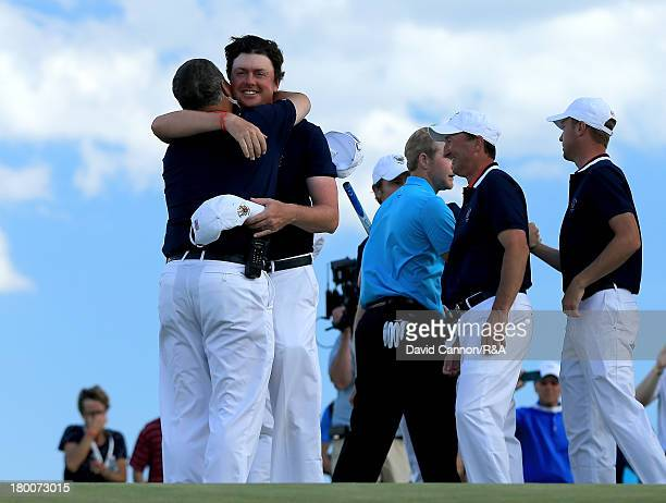 Nathan Smith of the United States team is embraced by his captain Jim Holtgrieve as Smith secured the winning point by beating Nathan Kimsey 4 and 3...