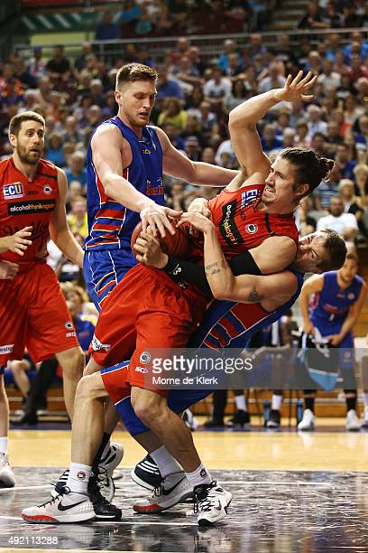 Nathan Sobey of the 36ers tackles Greg Hire of the Wildcats during the round one NBL match between Adelaide 36ers and the Perth Wildcats at Adelaide...