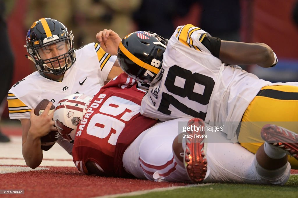 Nathan Stanley #4 of the Iowa Hawkeyes is sacked by Olive Sagapolu #99 of the Wisconsin Badgers during the second quarter of a game at Camp Randall Stadium on November 11, 2017 in Madison, Wisconsin.