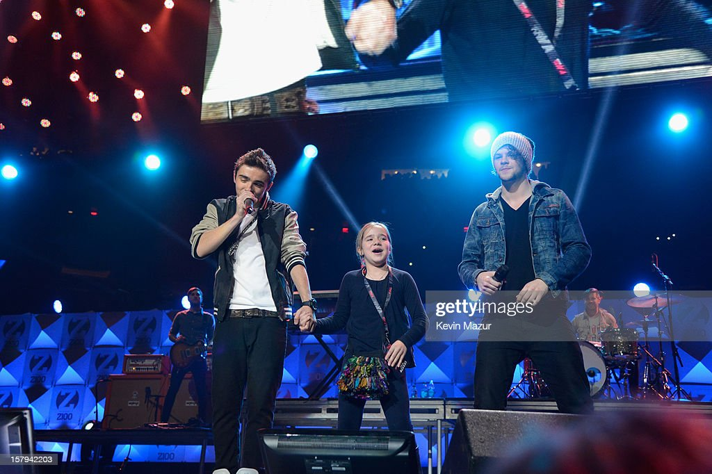 Nathan Sykes (L) and Jay McGuiness of The Wanted perform onstage with a fan during Z100's Jingle Ball 2012, presented by Aeropostale, at Madison Square Garden on December 7, 2012 in New York City.