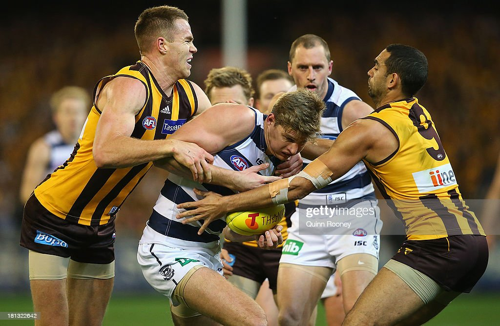 Nathan Vardy of the Cats is tackled by Max Bailey and Shaun Burgoyne of the Hawks during the AFL First Preliminary Final match between the Hawthorn Hawks and the Geelong Cats at the Melbourne Cricket Ground on September 20, 2013 in Melbourne, Australia.