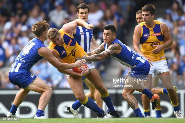 Nathan Vardy of the Eagles handballs whilst being tackled by Marley Williams of the Kangaroos during the round one AFL match between the North...