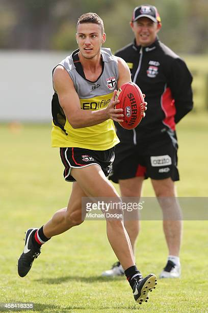 Nathan Wright runs with the ball in front of coach Alan Richardson during a StKilda Saints AFL training session at Linen House Oval on November 5...