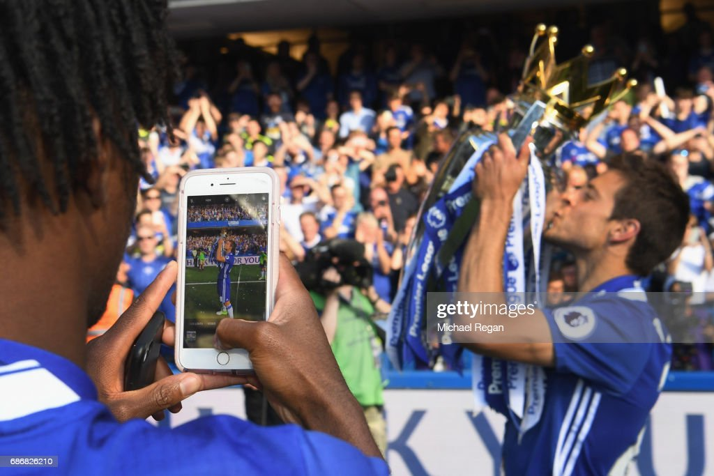 Nathaniel Chalobah of Chelsea takes a picture of team mate Cesar Azpilicueta and the Premier League Trophy on a phone after the Premier League match between Chelsea and Sunderland at Stamford Bridge on May 21, 2017 in London, England.