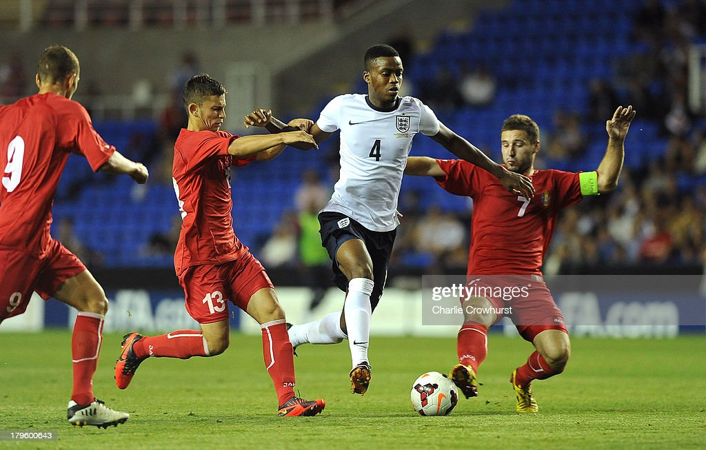 Nathaniel Chalobah #4 of England looks to skip the tackle from Igor Dima (R) and Eugen Zasaviitchi (L) of Moldova during the 2015 UEFA European U21 Championships Qualifier between England U21 and Moldova U21 at The Madejski Stadium on September 05, 2013 in Reading, England,
